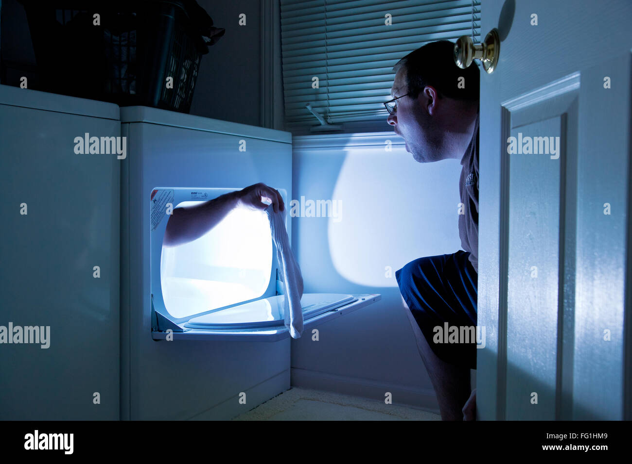 Side View Of Shocked Man Looking At Hand Holding Sock In Laundromat - Stock Image