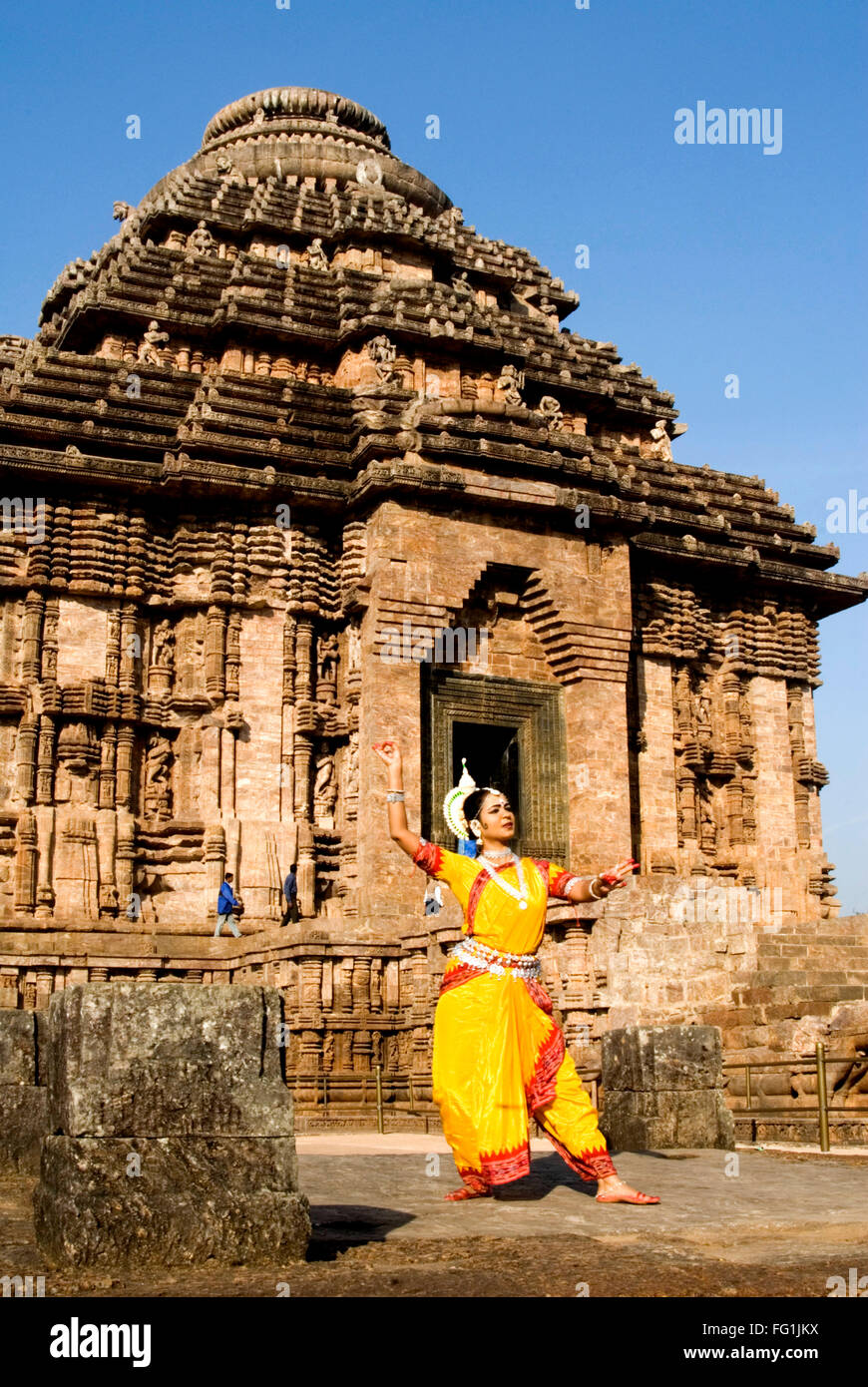Odissi dancer strikes pose of re enacts Indian myths such as Ramayana against backdrop Sun temple complex Konarak - Stock Image