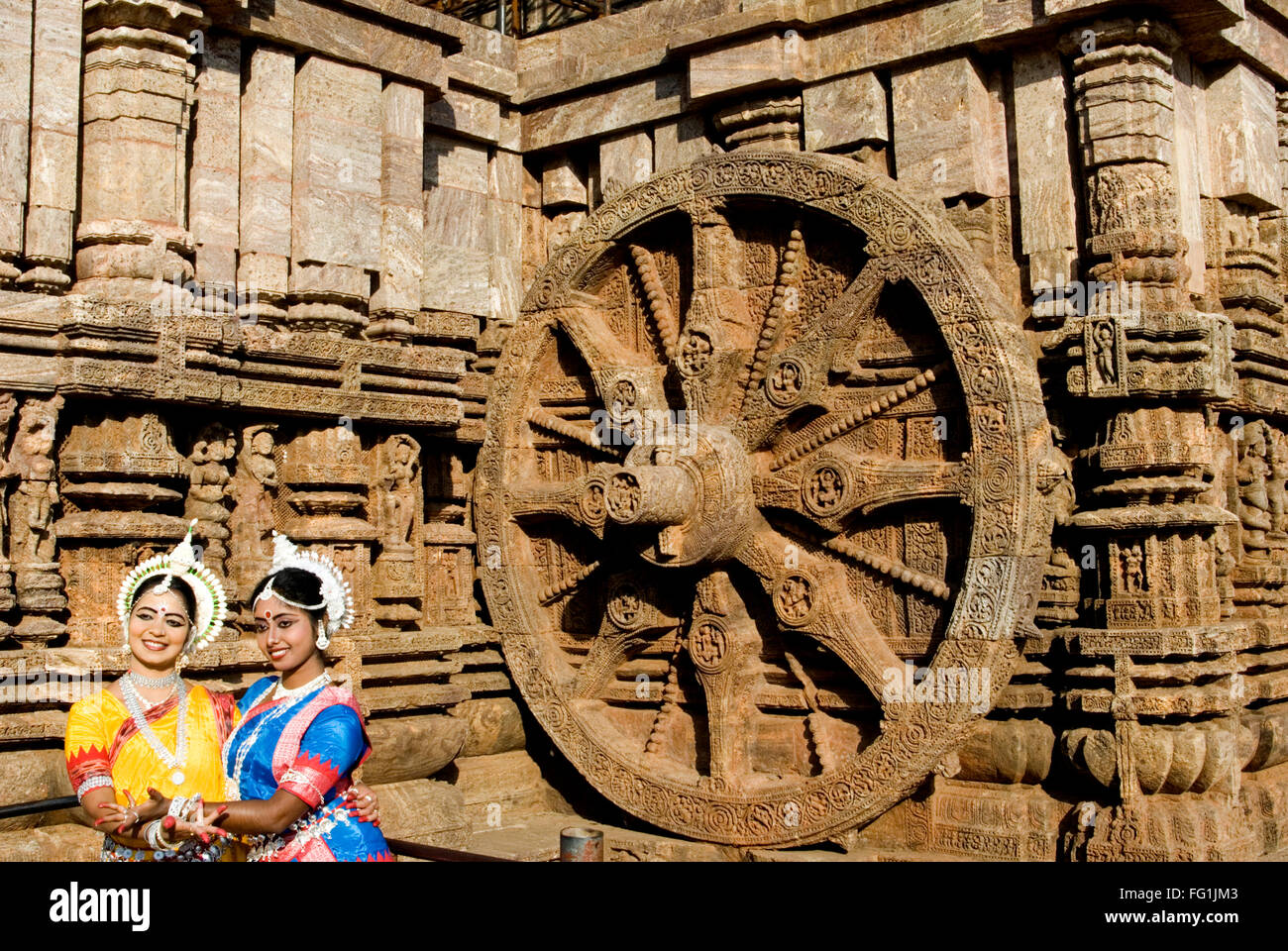 Odissi dancers strike pose re enacts Indian myths such as Ramayana front iconic Sun Chariot Sun temple complex Konarak - Stock Image