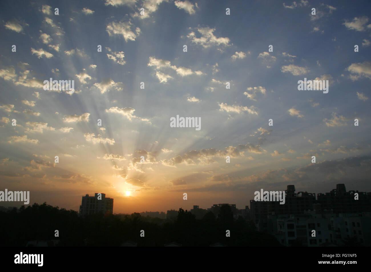 Glorious sunrise with white fluffy clouds and blue skies , Pune ,  Maharashtra ,  India - Stock Image