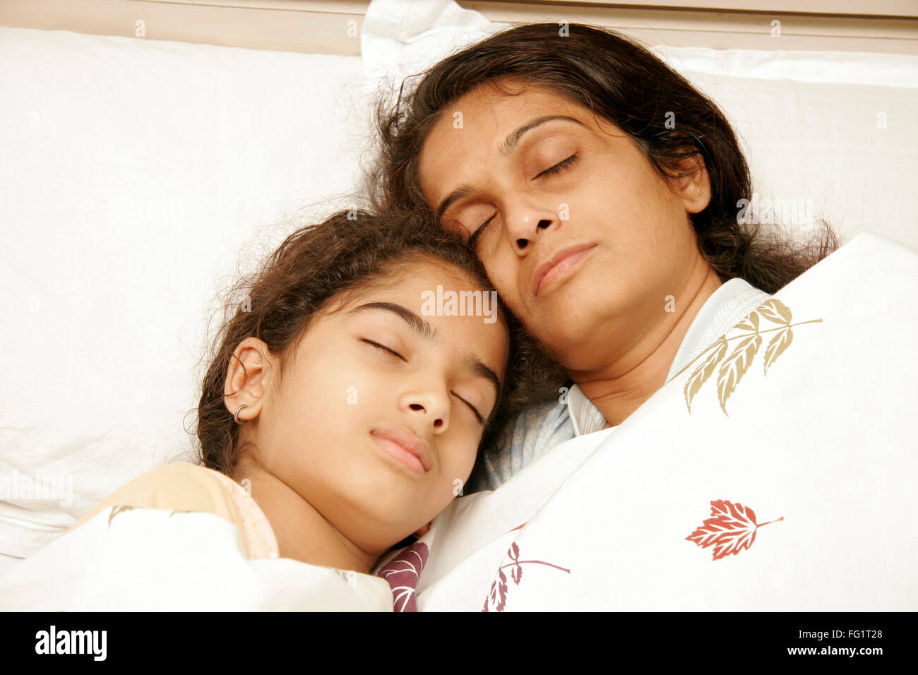 South Asian Indian mother and daughter having sound asleep on bed  MR#191,189 - Stock