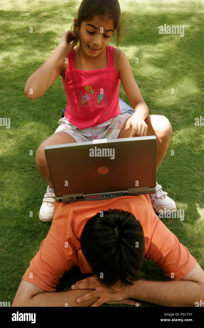 South Asian Indian younger sister sitting on back of elder brother and operating laptop MR#686C,191 - Stock Image