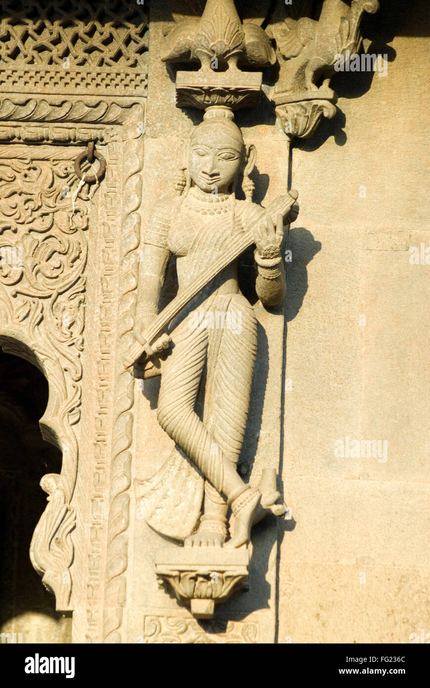 Woman playing veena music instrument carved in stone on wall of ...