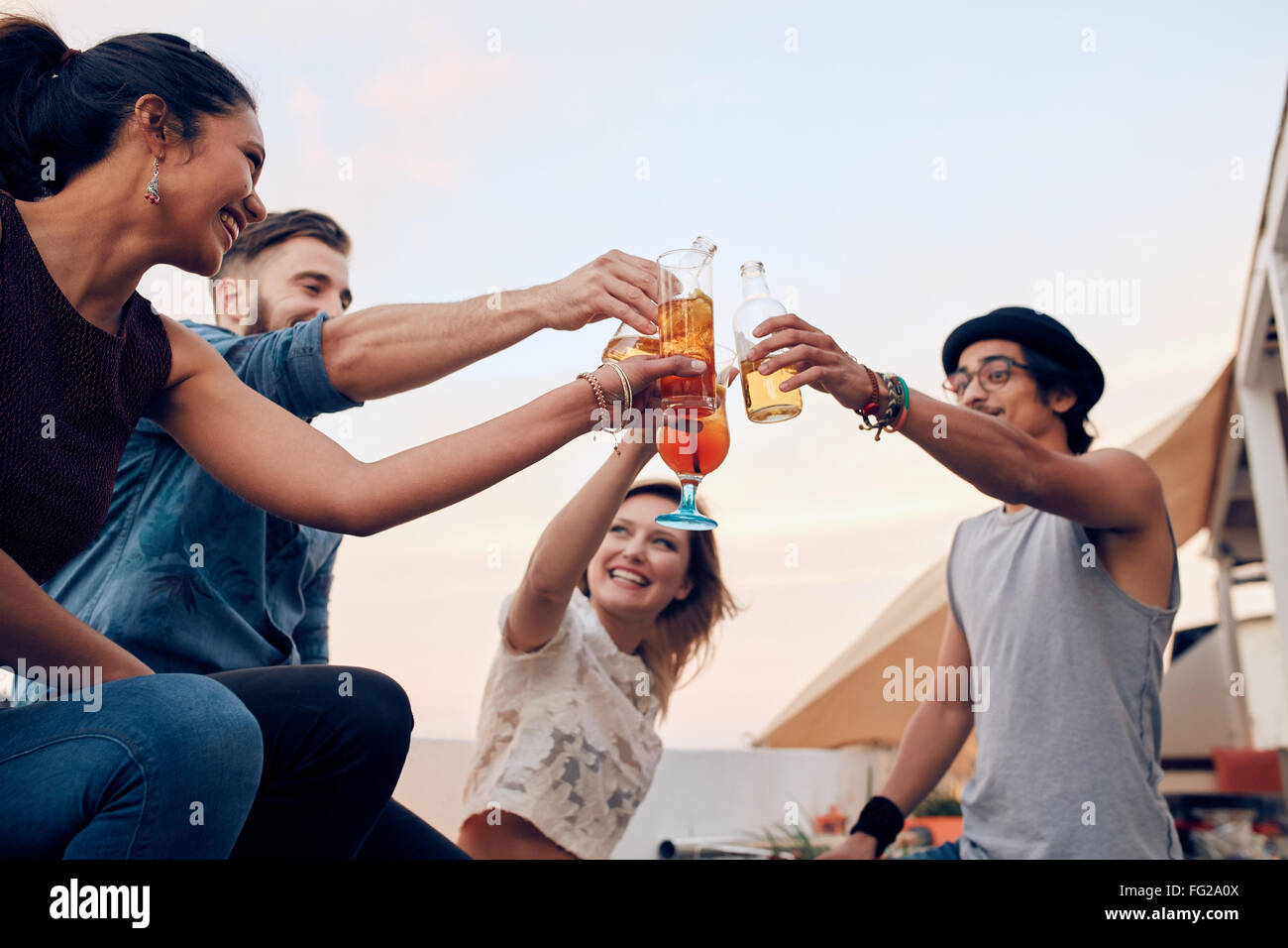Portrait of young people toasting cocktails during a party. Four young friends enjoying in a party. Young man and - Stock Image