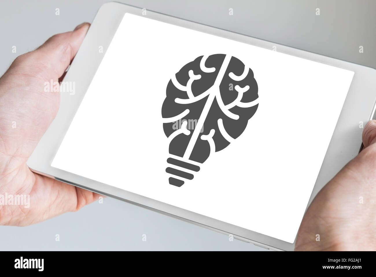 Mobile digital innovation concept visualized by brain and light bulb symbol displayed on touchscreen of modern template - Stock Image