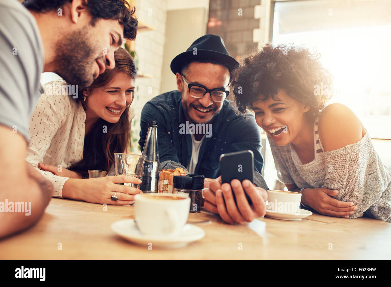 Portrait of cheerful young friends looking at smart phone while sitting in cafe. Mixed race people sitting at a - Stock Image