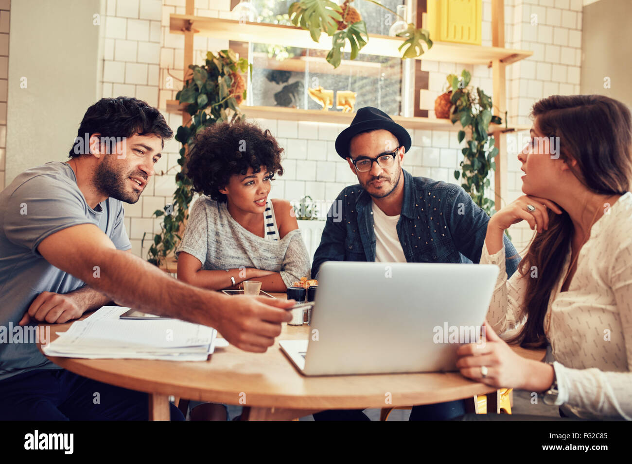 Portrait of young people sitting around a table in cafe with a laptop. Creative team discussing new business project - Stock Image