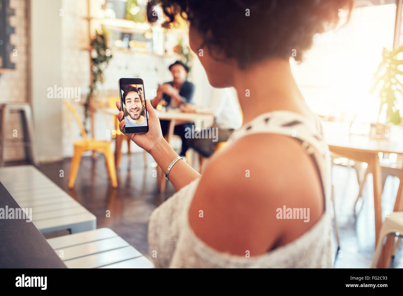 Man and woman talking to each other through a video call on a smartphone. Young woman having a videochat with man - Stock Image