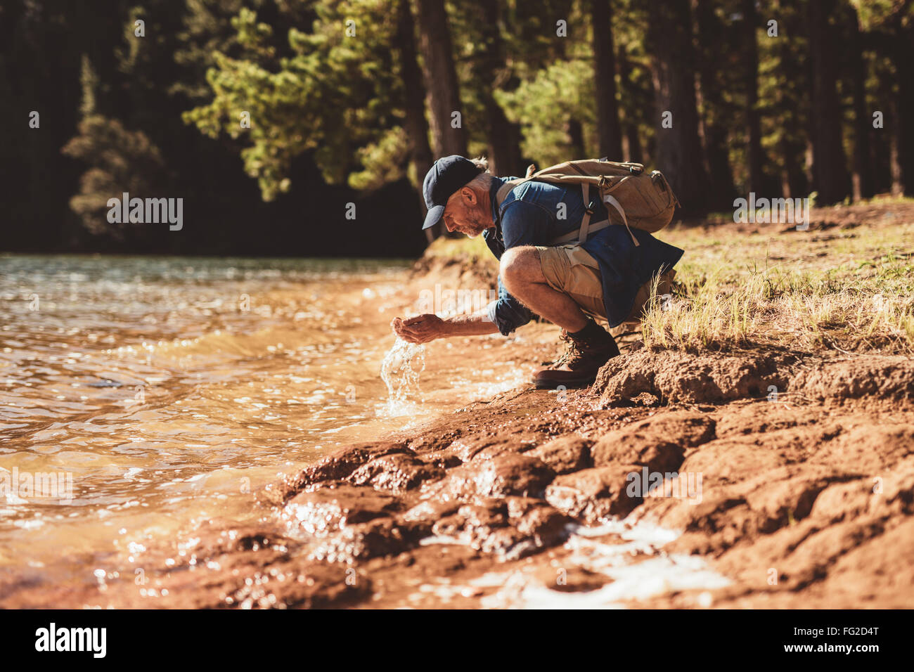 Portrait of mature man washing his face with lake water. Senior caucasian man washing face from lake water on a - Stock Image