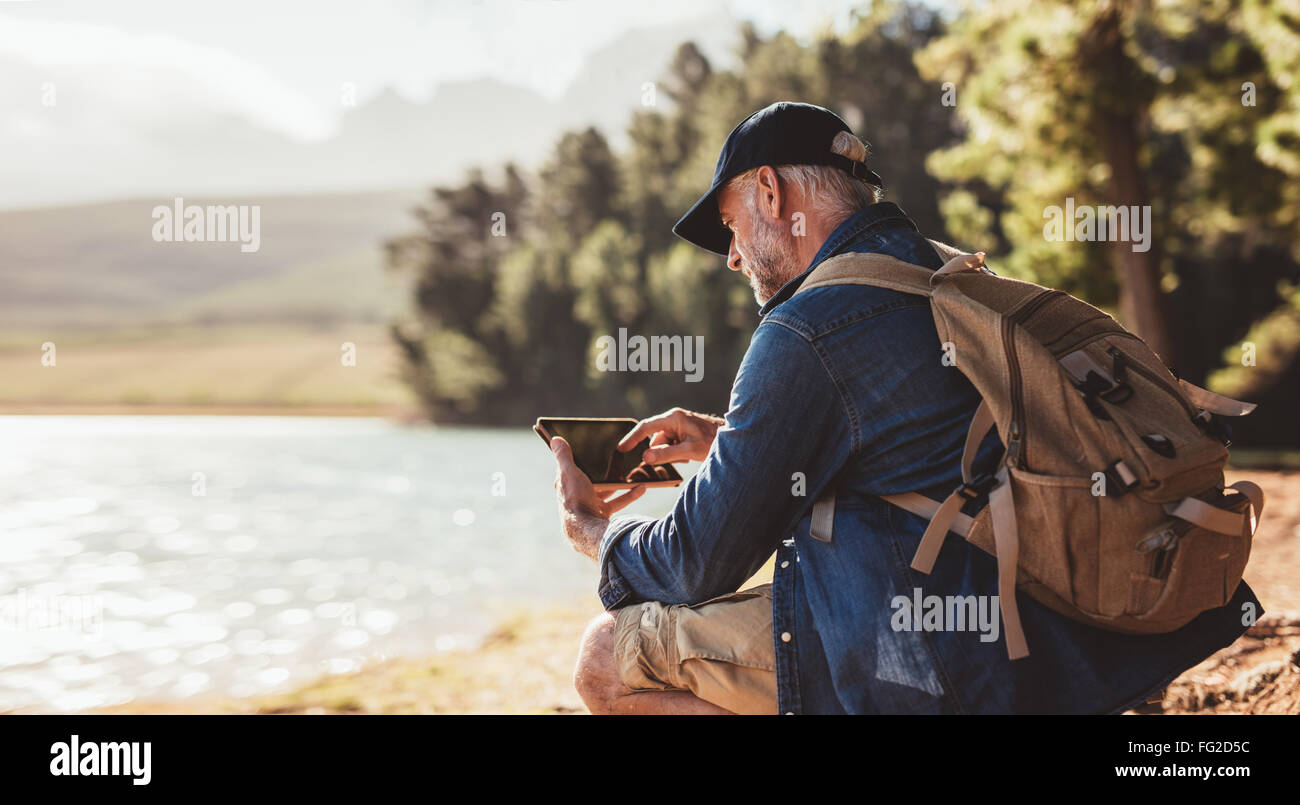 Senior man with backpack using digital tab while sitting near a lake. Mature man on hike in nature using digital - Stock Image