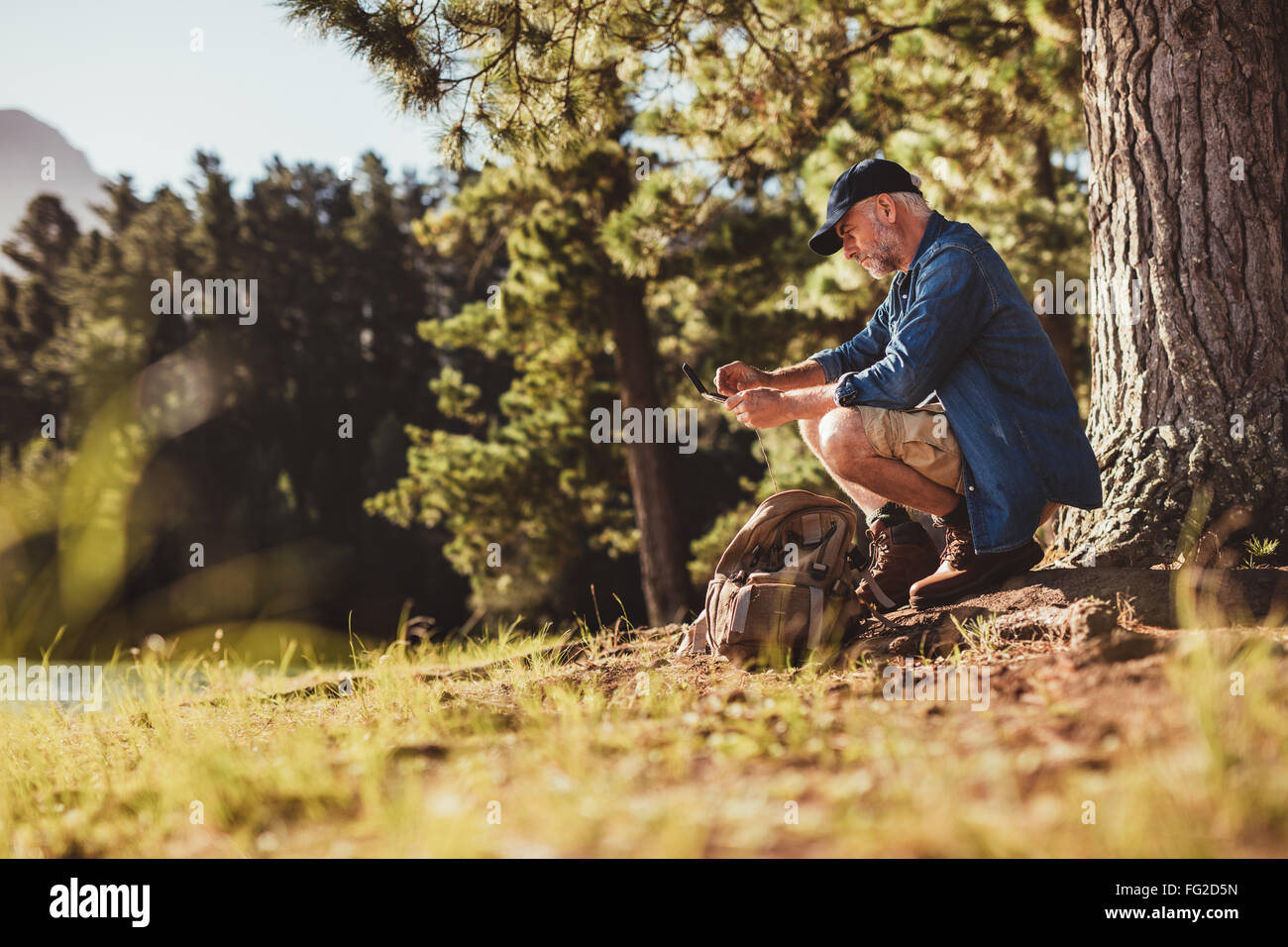 Portrait of senior hiker checking his compass. Mature man sitting by a tree searching for direction. - Stock Image