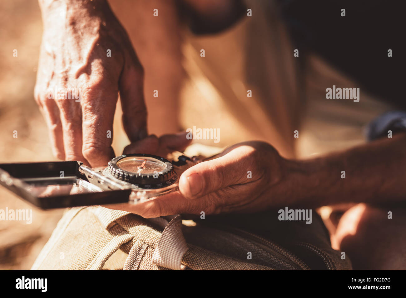 Close up portrait of man using compass for directions. Focus on compass in hands of a male hiker. - Stock Image