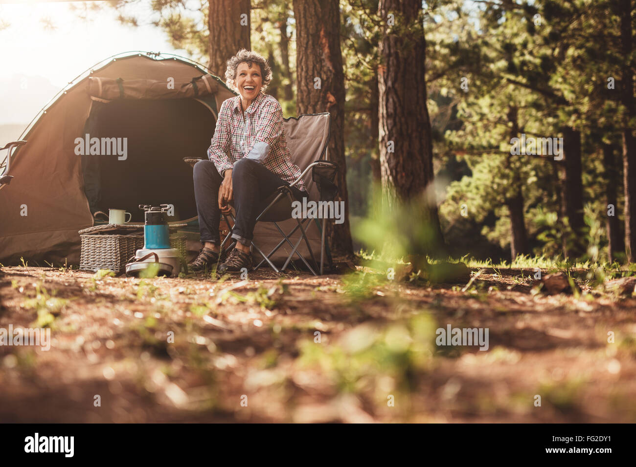 Senior woman sitting relaxed outside a tent. Smiling mature woman camping in forest. - Stock Image