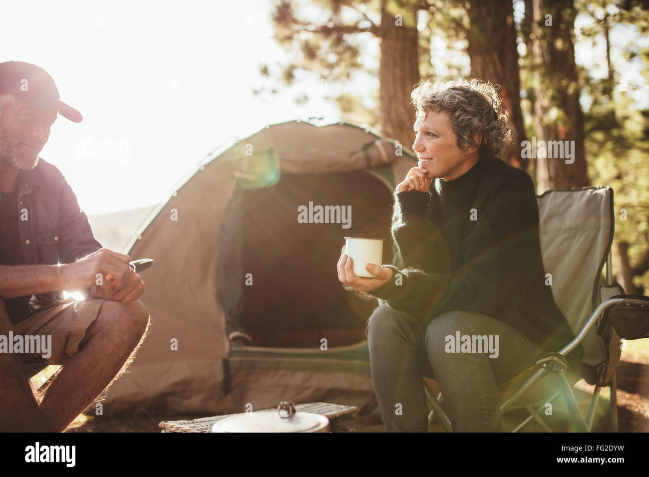 Portrait of relaxed mid adult couple sitting outside tent while camping nearby lakeside on a sunny day. Woman holding - Stock Image