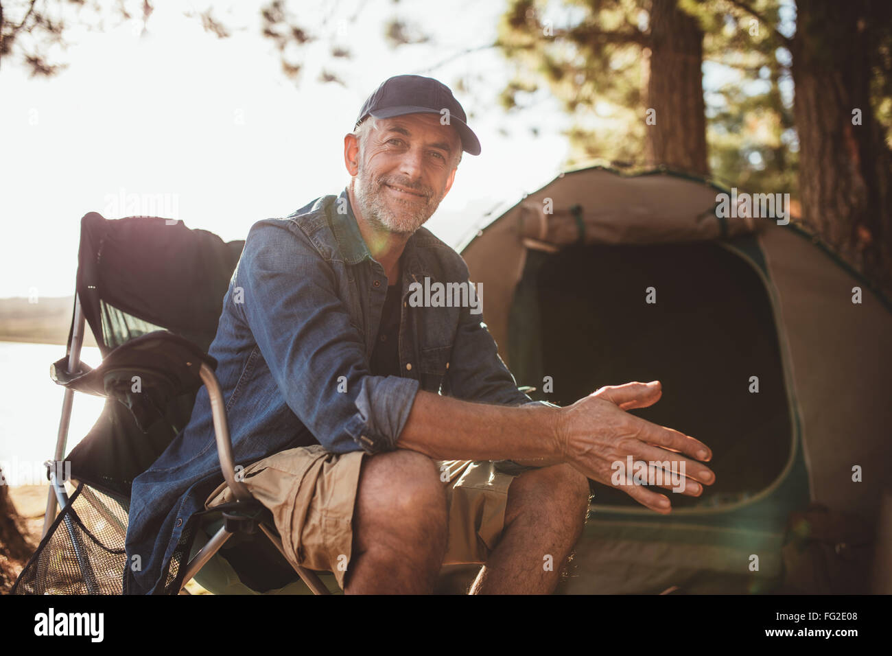 Portrait of a happy mature man sitting in front of a tent and looking at camera. Senior caucasian man at campsite. - Stock Image