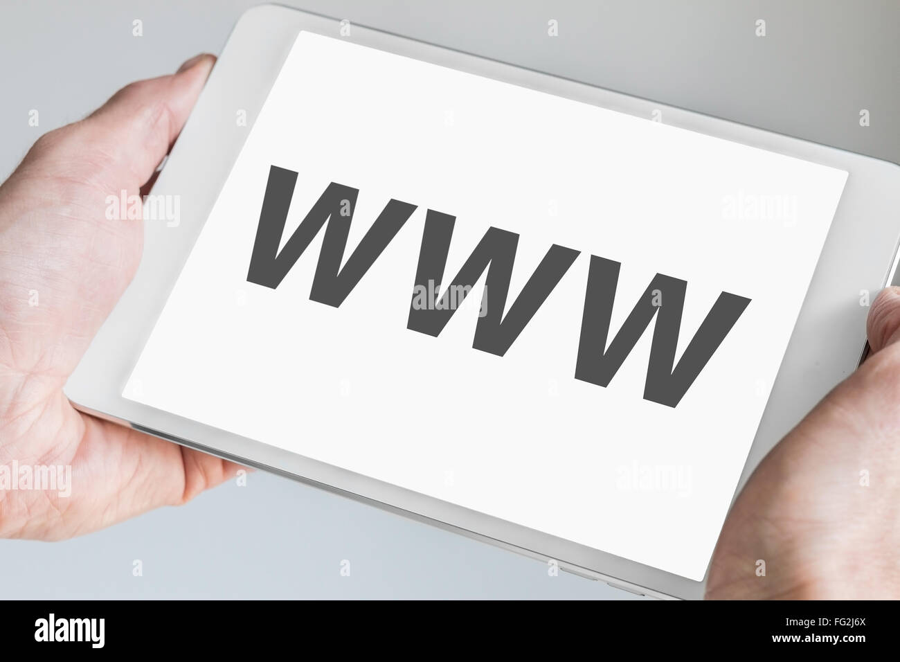 WWW (world wide web) text displayed on touch screen of modern tablet. Hands holding white mobile device - Stock Image