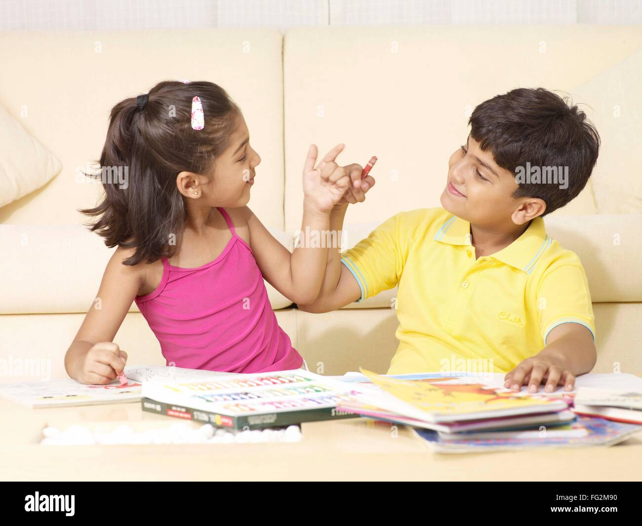 Brother and sister doing naughty expression sitting in house MR#702T, MR#702U Stock Photo