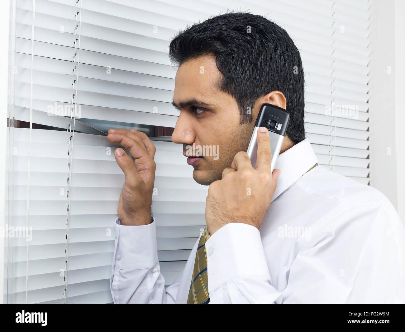 Multitasking executive peeping through venetian blind MR#779K - Stock Image