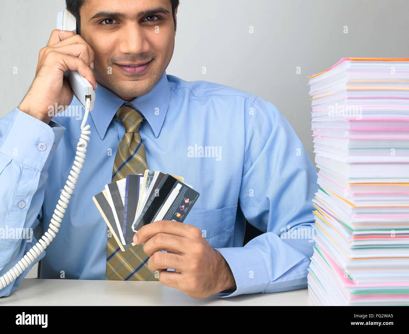 Multitasking executive talking on telephone with showing credit cards MR#779K Stock Photo