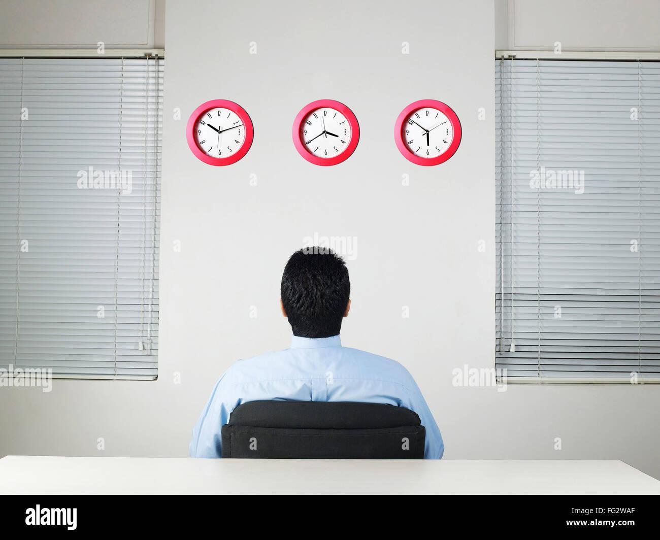 Executive looking at row of clocks MR #779K - Stock Image