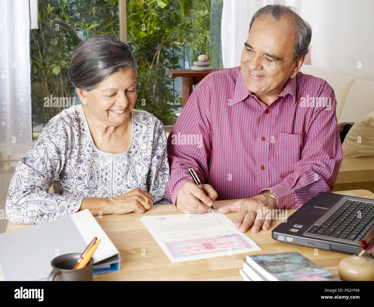 Old couple preparing legal document signing on stamp paper - MR#702T,702S - Stock Image