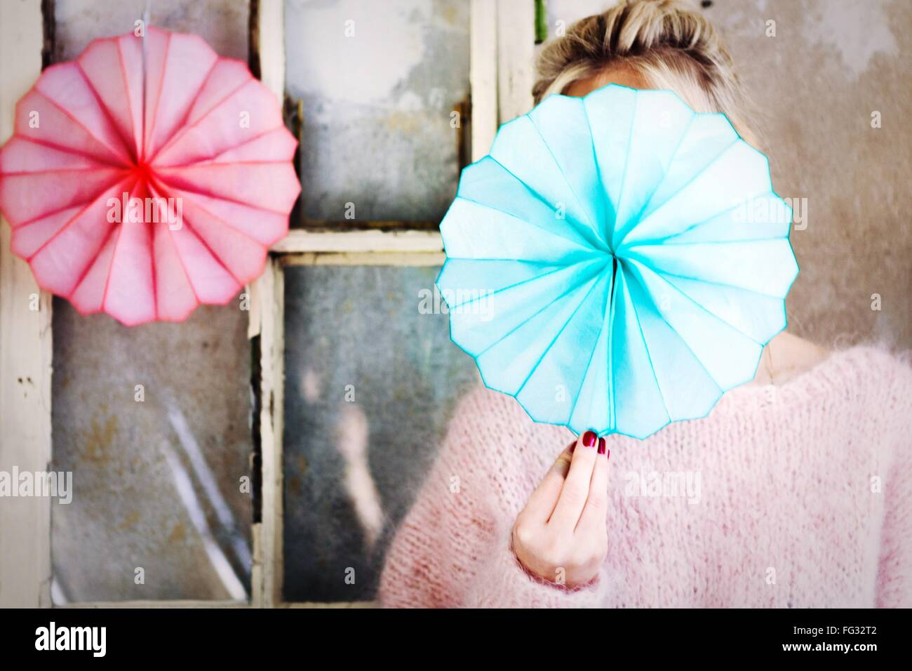 Woman Holding Blue Handmade Paper Fan In Front Of Face - Stock Image
