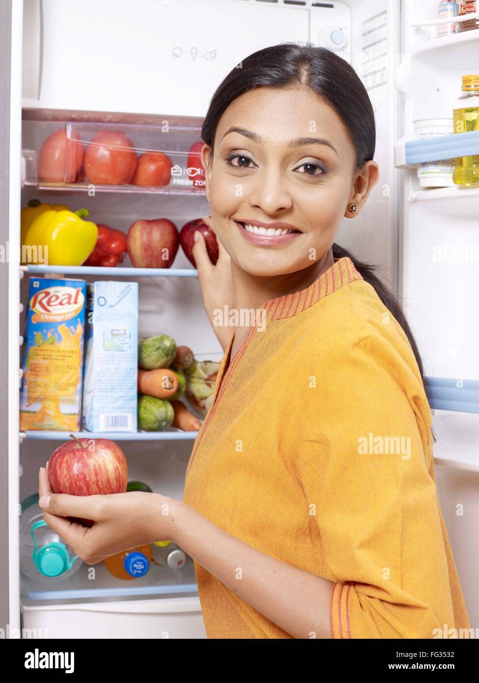 Young lady kept red apple in refrigerator MR#702U - Stock Image