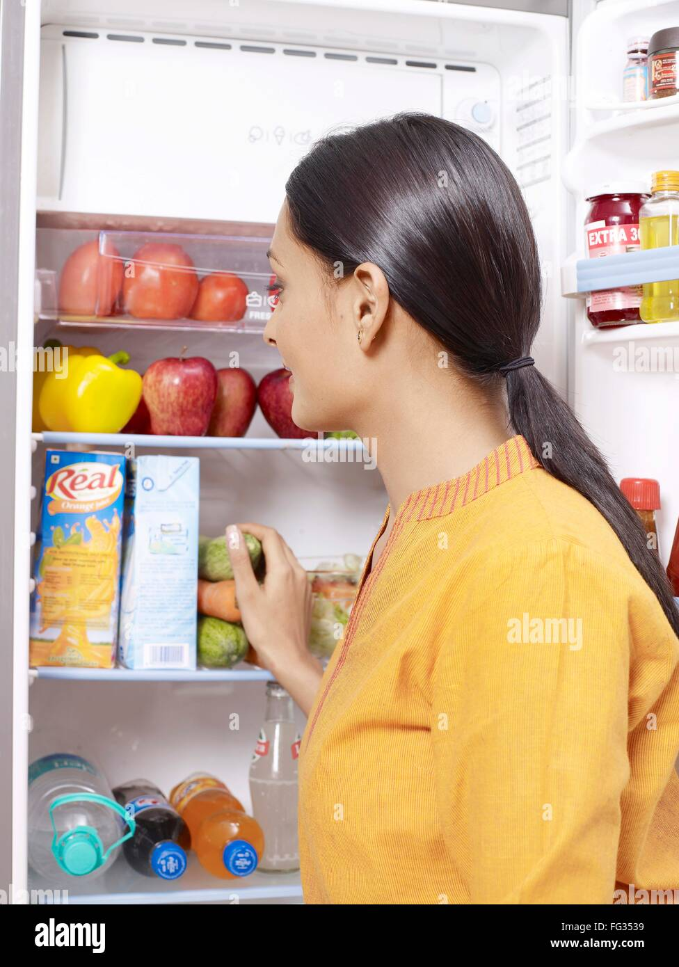 Young lady looking at open refrigerator MR#702U - Stock Image