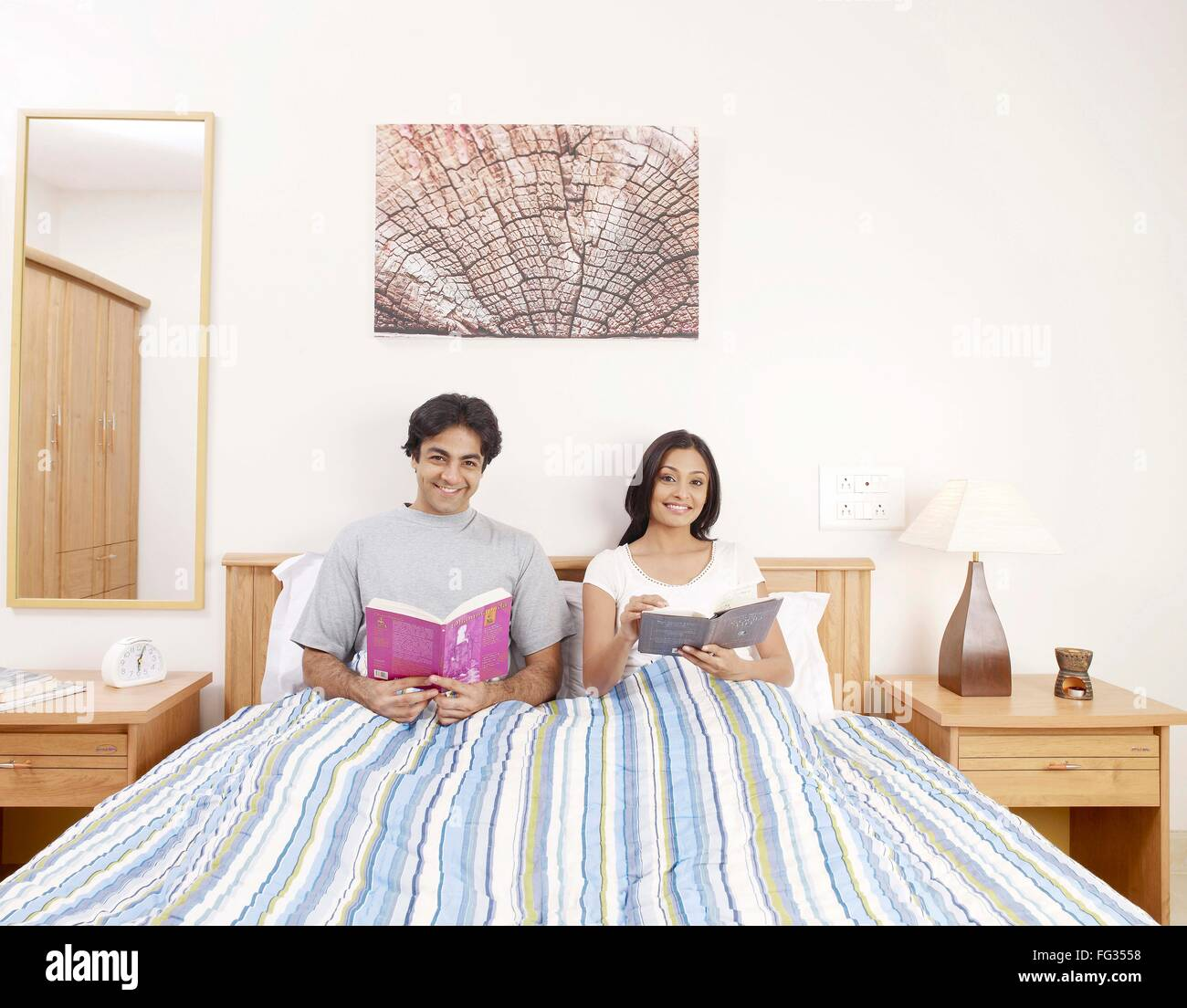 Young man and woman holding novels sitting on bed MR#702V,702U - Stock Image