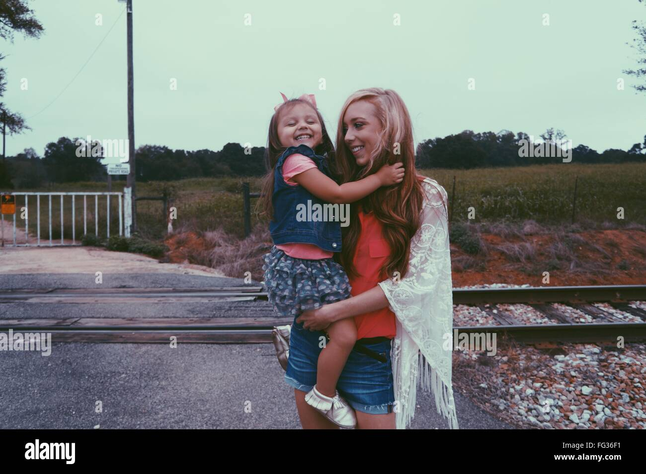 Mother Carrying Daughter Against Railroad Crossing - Stock Image
