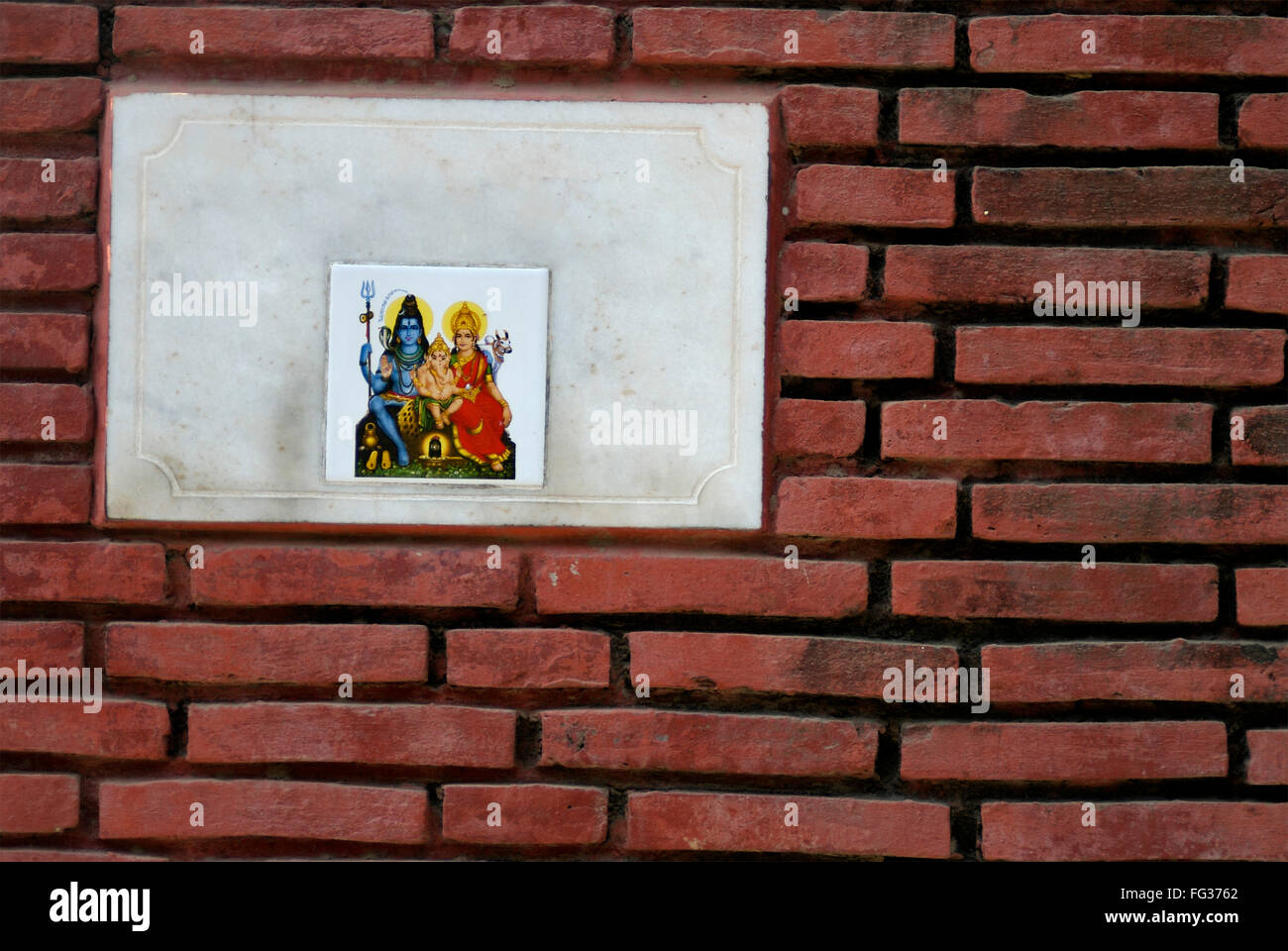 Red brick wall with tile designed with impression of god Shiva goddess Parvati and Lord Ganesha - Stock Image