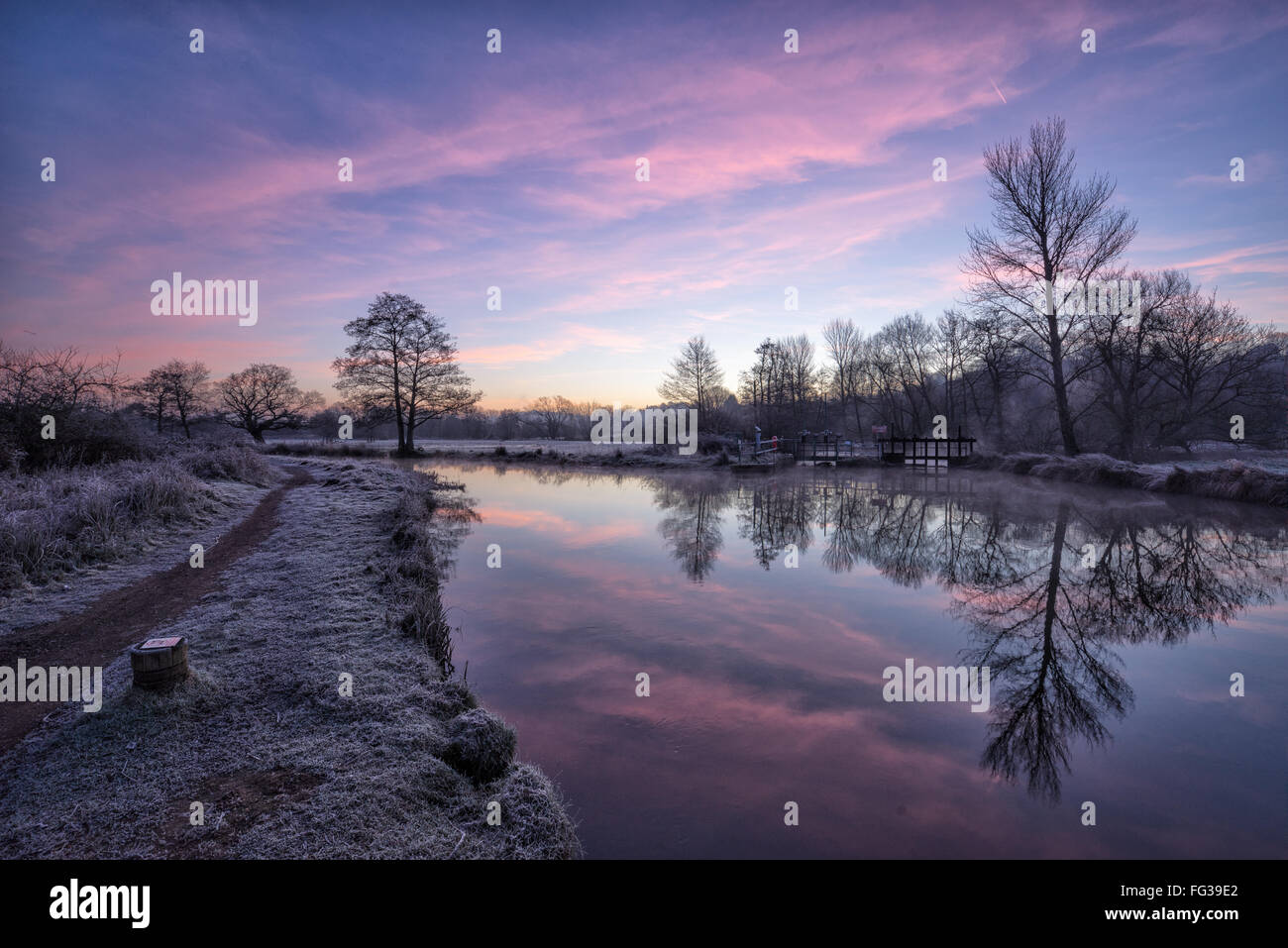 Sunrise over the river Wey navigation with frost on the ground and trees reflected in the river - Stock Image