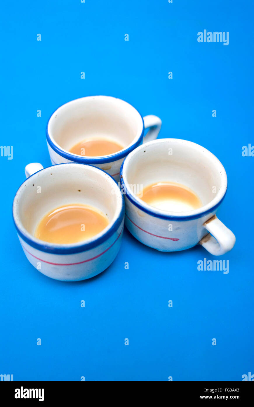 Three empty cups of tea on blue table ; Dhaka ; Bangladesh - Stock Image