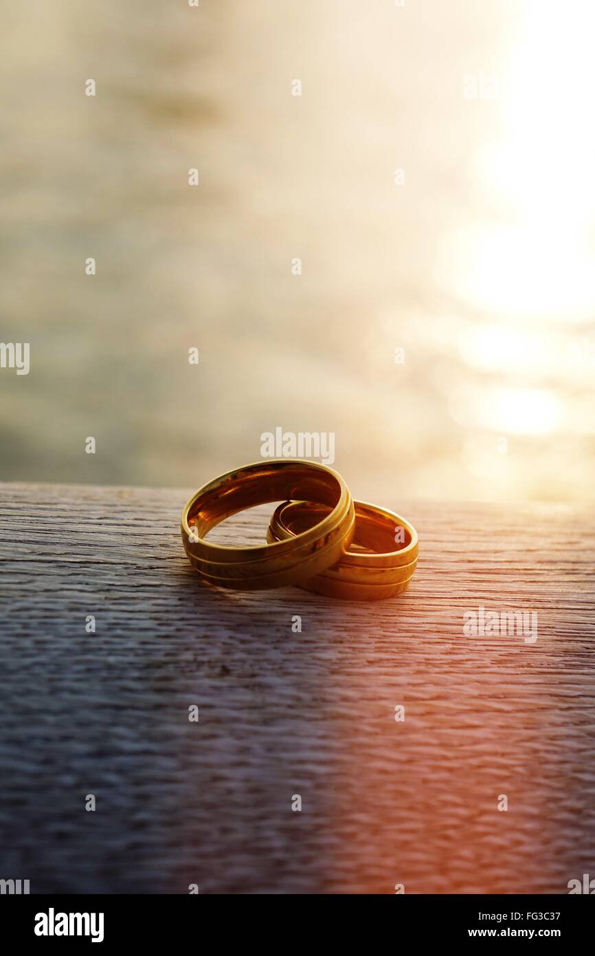 Close-Up Of Wedding Rings In Front Of Sea During Sunset - Stock Image
