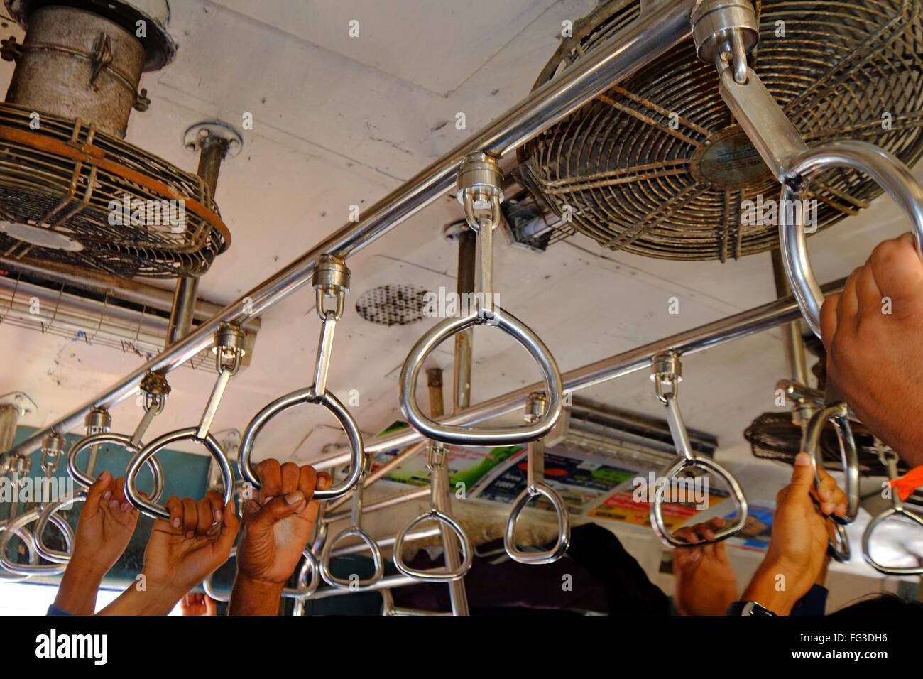 Commuters hang on in a suburban rail carriage, Mumbai India Stock Photo
