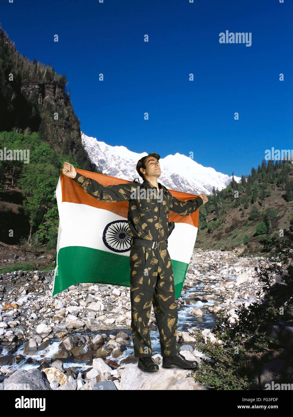 Indian army soldier holding national flag on his backside mountain in background MR Stock Photo