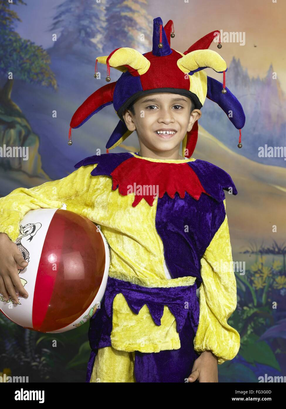 1a8a5abef South Asian Indian boy dressed as joker holding ball performing fancy dress  competition on stage in nursery school MR