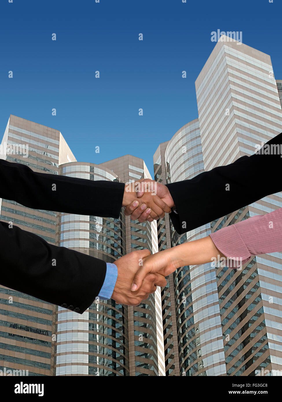 Executives handshaking skyscraper in background MR - Stock Image