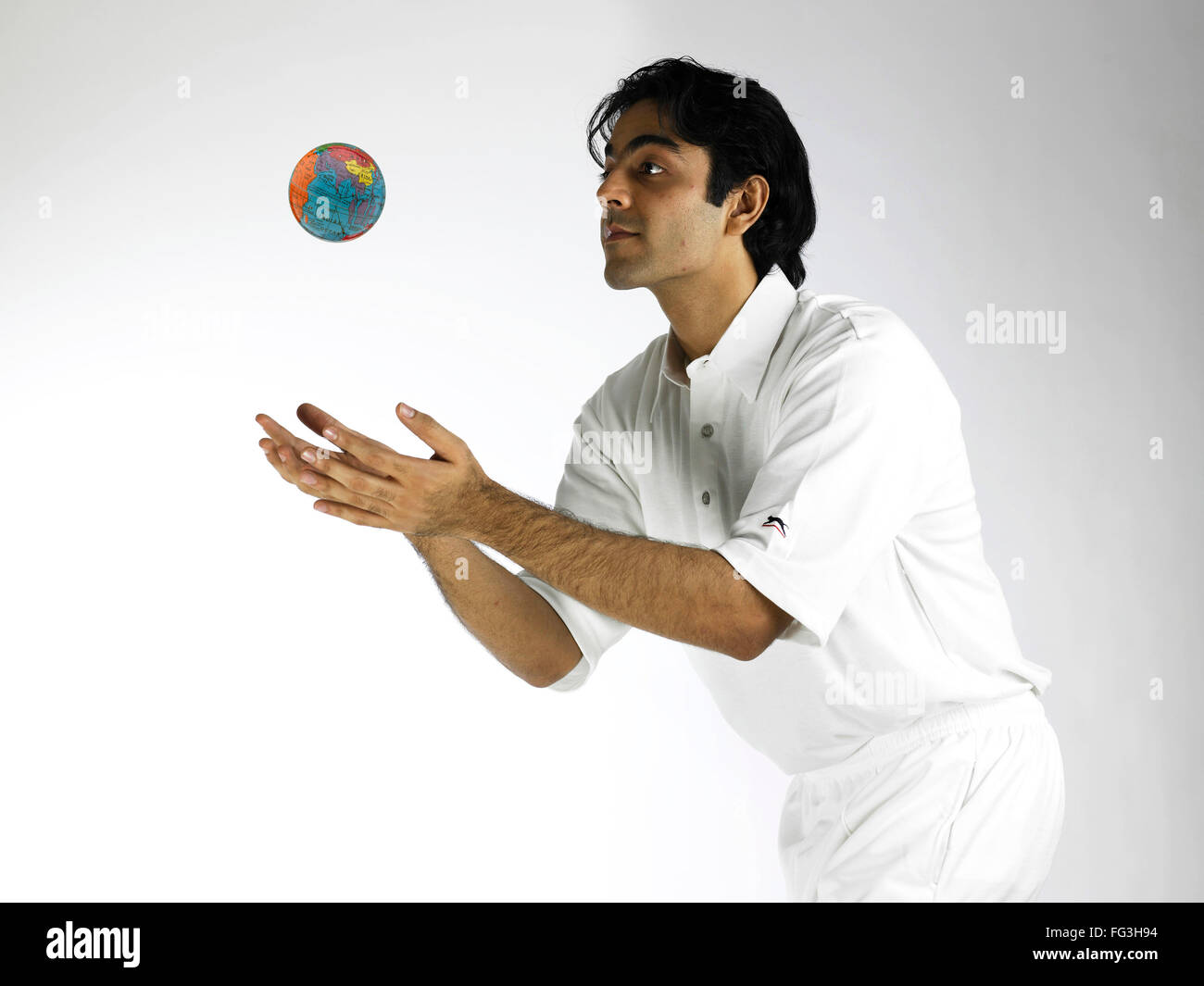 Indian bowler in action of catching globe MR#702A - Stock Image