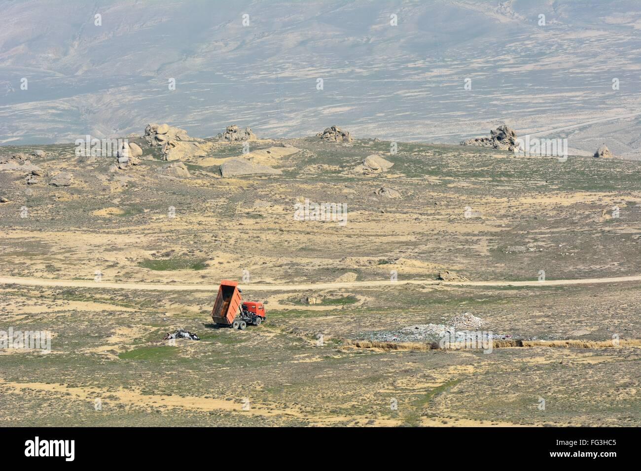 Truck dumping rubbish in Azerbaijani countryside. Trash is improperly dumped in open countryside in Lokbatan, near - Stock Image