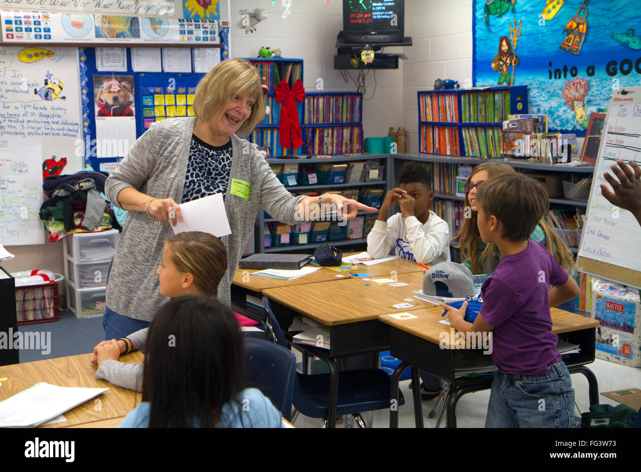 Teacher in fourth grade classroom with students, USA. - Stock Image