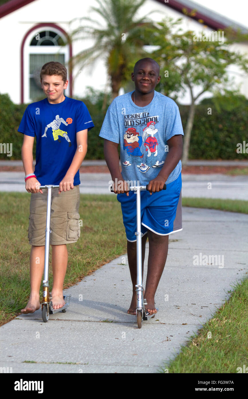 Two 11 year old boys riding scooters in Florida, USA. - Stock Image