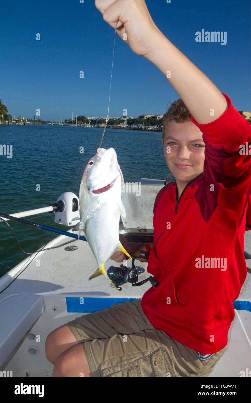 11 year old boy holding up his catch of a Jack Cravalle saltwater fish in Florida, USA. MR - Stock Image