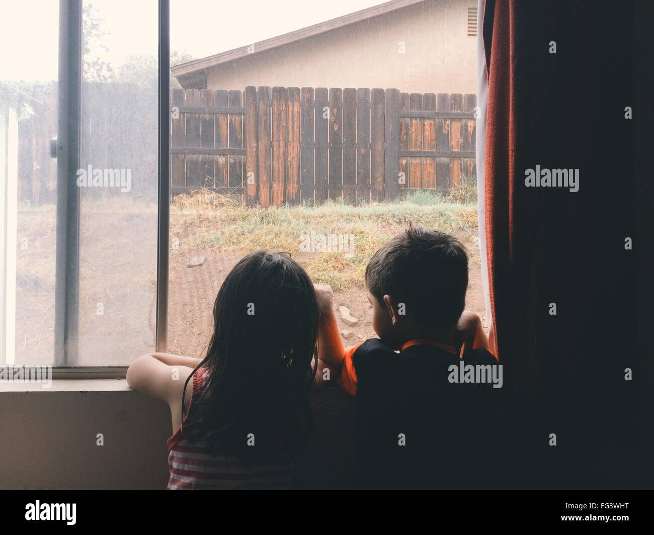 Rear View Of Siblings Looking Through Window At Home - Stock Image