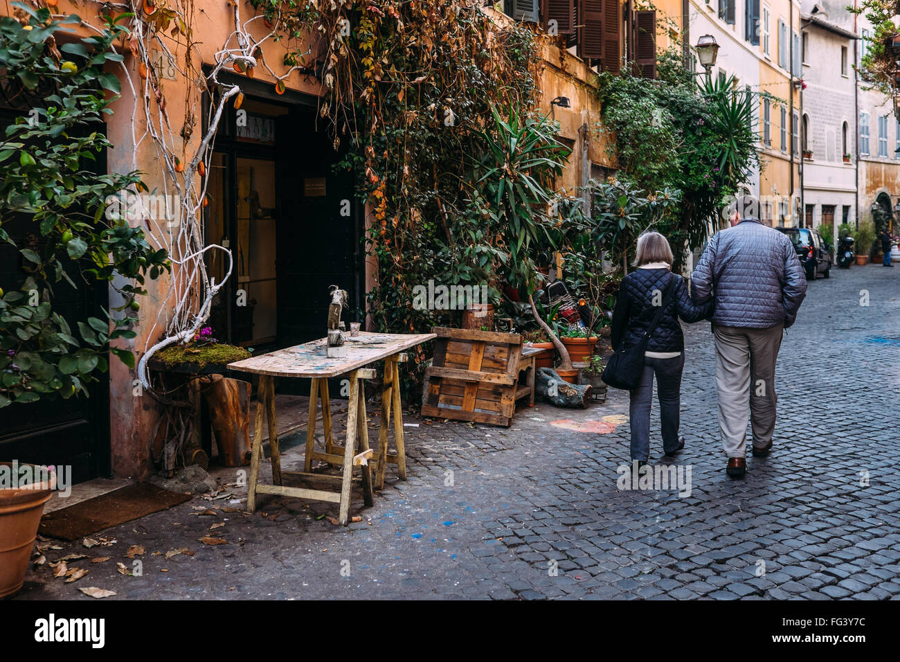 A couple strolls down Via dei Cappellari, a characteristic street full of artisans in Rome, Italy - Stock Image
