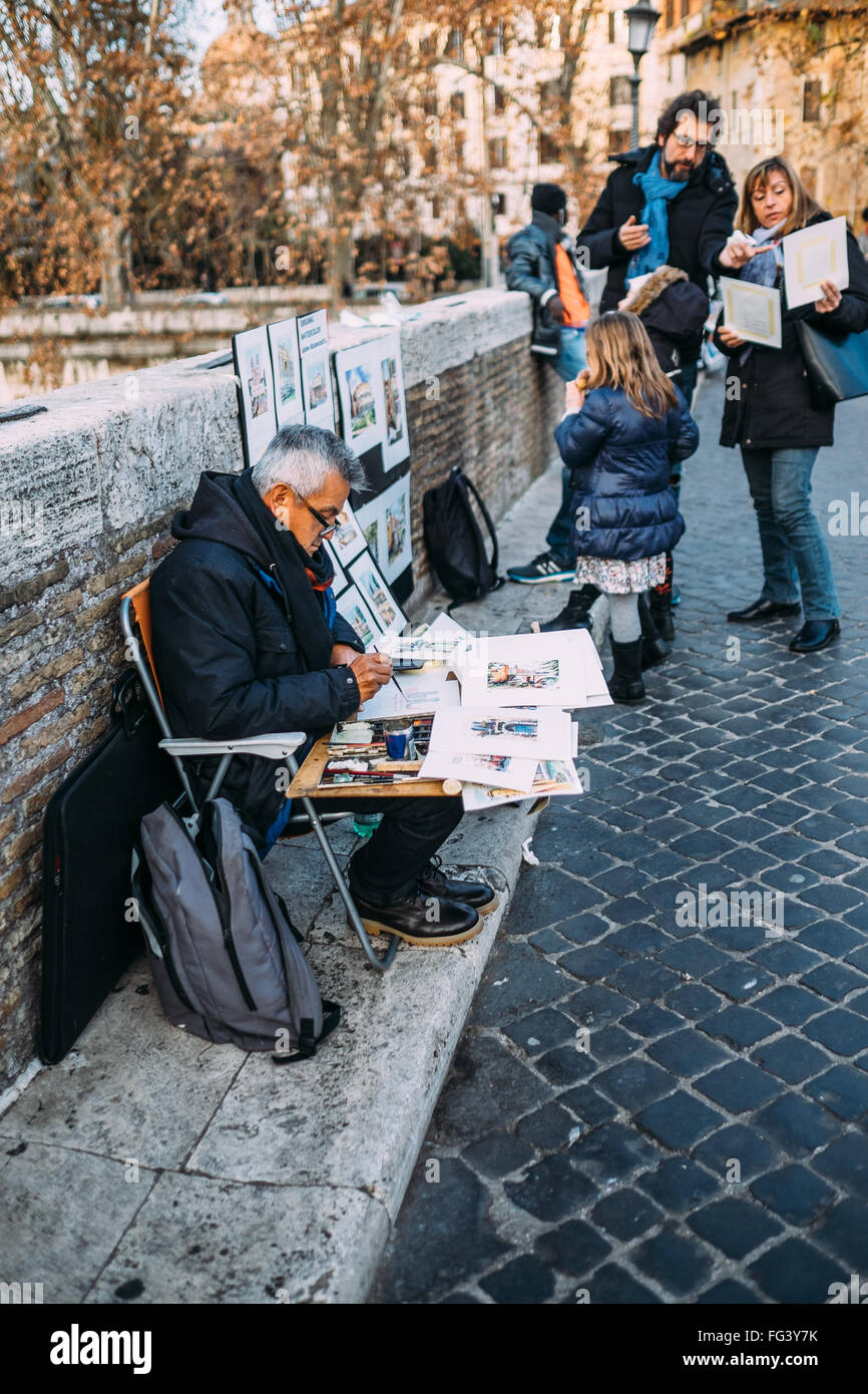 An artist paints scenes of Rome from Ponte Fabricio while a family in the background looks through his paintings. - Stock Image