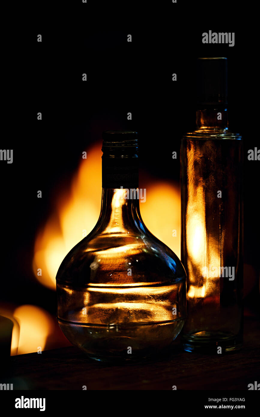 Two transparent glass bottles in front of a fire - Stock Image