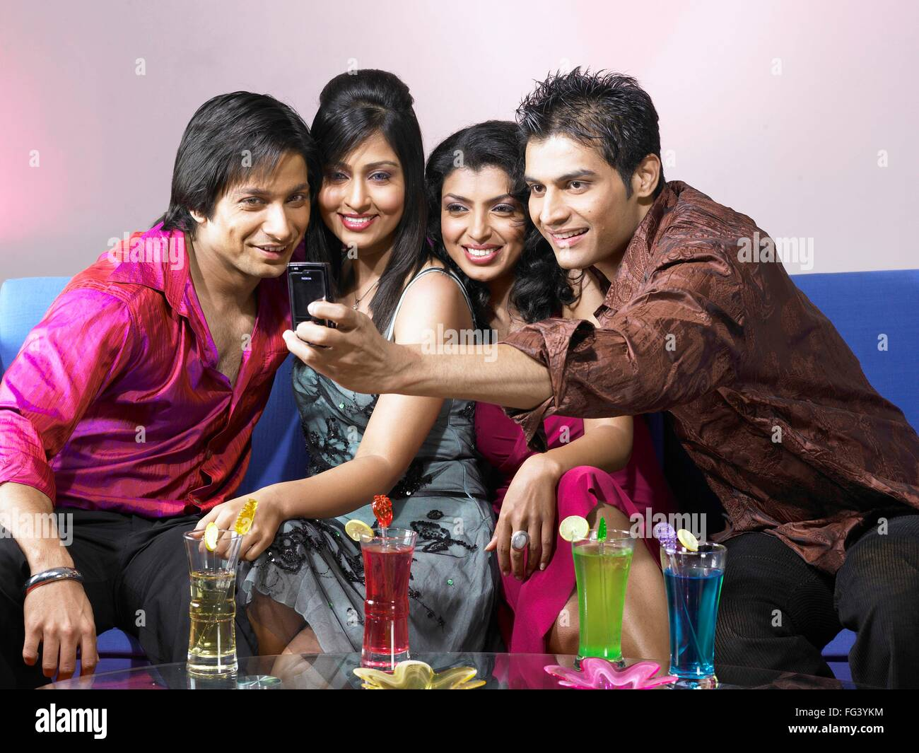 South Asian Indian man taking group photo in mobile celebrating party MR - Stock Image