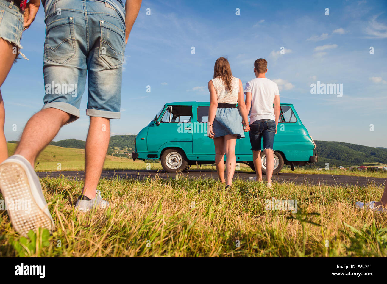 Couples in love, nature, blue sky, campervan, back view - Stock Image