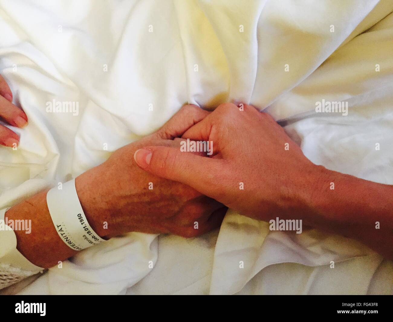 Cropped Image Of Man Holding Woman Hand On Bed At Home - Stock Image